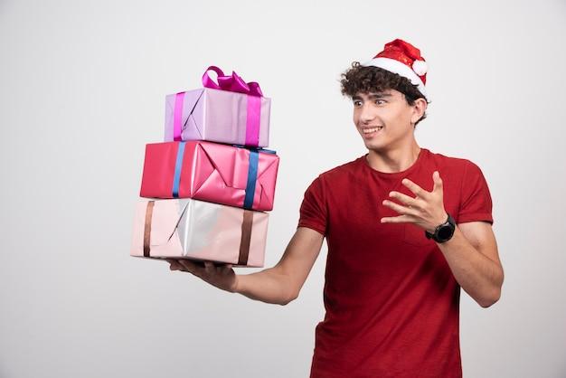 Jonge man in kerstmuts met geschenken met tevreden uitdrukking.