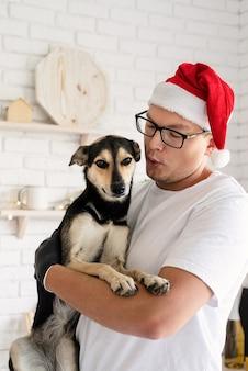 Jonge man in kerstmuts met zijn hond in zijn armen in de keuken
