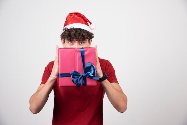 Jonge man in kerstmuts verstopt achter geschenkdoos.