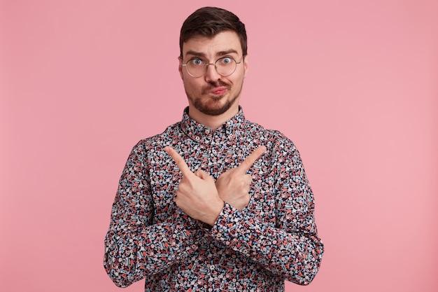 Jonge man in kleurrijk shirt kijkt door een bril met twijfels en met verwarde gezichtsuitdrukking houdt de handen gekruist en wijst naar de zijkanten van de mond met inde vingers geïsoleerd op roze achtergrond