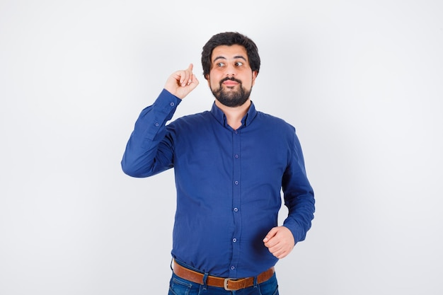 Jonge man in koningsblauw overhemd dat naar achteren wijst en aandachtig kijkt, vooraanzicht.