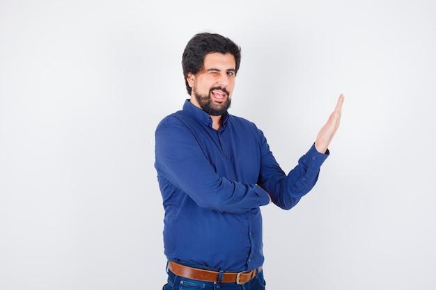 Jonge man in koningsblauw shirt knipogend terwijl hij open palm opzij spreidt, vooraanzicht.