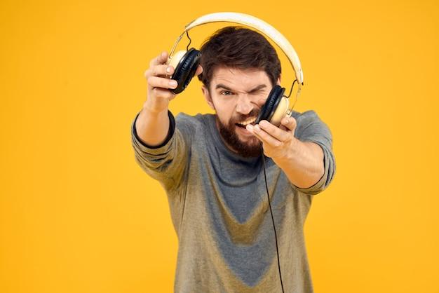 Jonge man in koptelefoon in handen emotioneel poseren