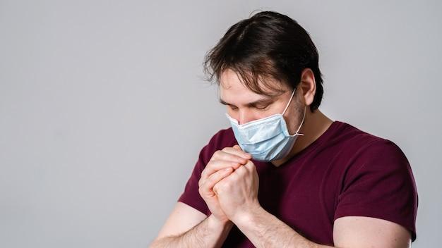 Jonge man in masker, bidden voor redding en bescherming tegen gevaarlijke virussen.