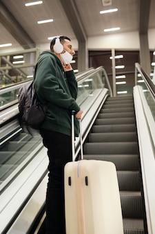 Jonge man in masker met bagage op transportband in luchthaven klaar om te reizen