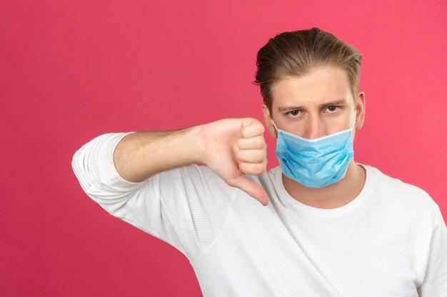 Jonge man in medisch beschermend masker op zoek triest duimen omlaag tonen afkeer over geïsoleerde roze achtergrond