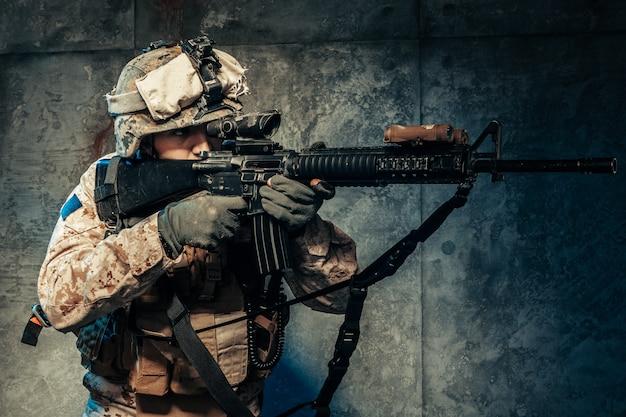 Jonge man in militaire outfit een huursoldaat in moderne tijden op een donkere achtergrond in de studio