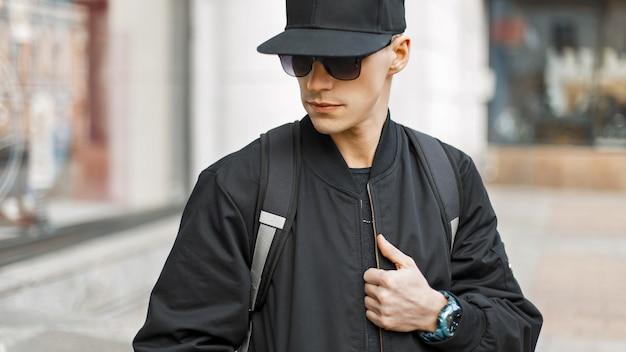 Jonge man in mode zonnebril in een zwarte pet en jas met een tas in de stad