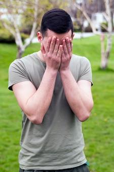 Jonge man in openbaar park met een hoofdpijn en veel problemen, houdt zijn hoofd.