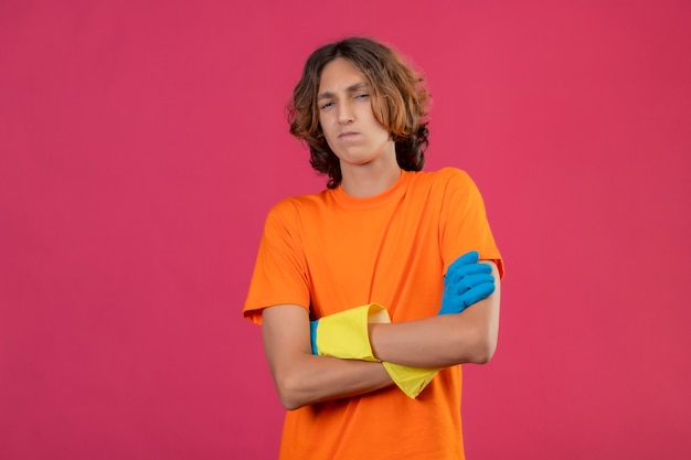 Jonge man in oranje t-shirt dragen rubberen handschoenen bedrijf staande met gekruiste armen kijken camera zelfverzekerd staande over roze achtergrond