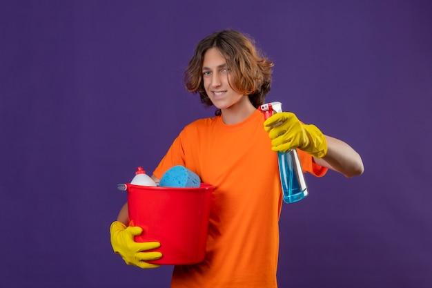 Jonge man in oranje t-shirt dragen rubberen handschoenen emmer met schoonmaakmiddelen houden en schoonmaak spray camera kijken met zelfverzekerde glimlach op gezicht staande over paarse achtergrond