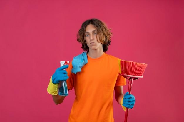 Jonge man in oranje t-shirt dragen rubberen handschoenen met dweil en reinigingsspray camera kijken met ernstige en zelfverzekerde uitdrukking op gezicht staande over roze achtergrond