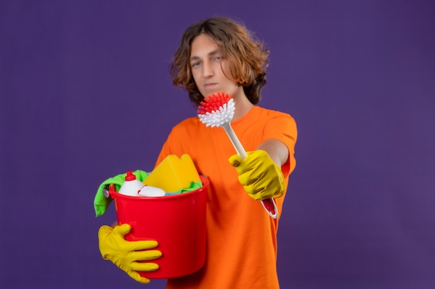 Jonge man in oranje t-shirt dragen rubberen handschoenen met emmer met schoonmaakgereedschap tonen schrobborstel naar camera op zoek zelfverzekerd staande over paarse achtergrond
