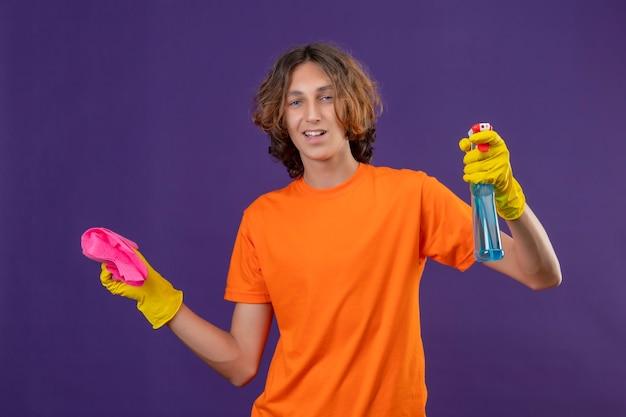 Jonge man in oranje t-shirt dragen rubberen handschoenen met schoonmaak spray en tapijt camera kijken met zelfverzekerde glimlach staande over paarse achtergrond