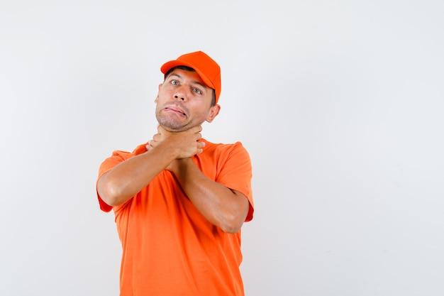 Jonge man in oranje t-shirt en pet die aan keelpijn lijdt en ziek kijkt