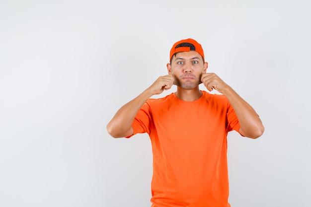 Jonge man in oranje t-shirt en pet die zijn wangen trekt en geliefd kijkt
