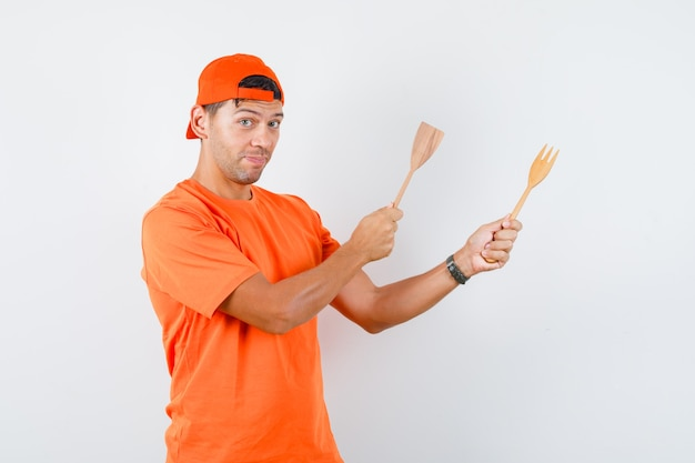 Jonge man in oranje t-shirt en pet met houten vork en spatel en grappig kijken