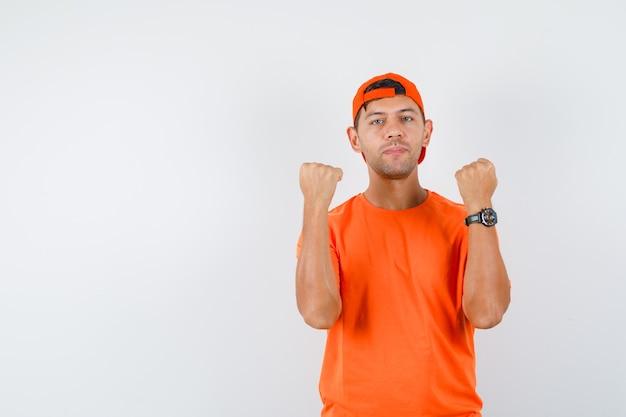 Jonge man in oranje t-shirt en pet met opgeheven vuisten gebalde en op zoek zelfverzekerd
