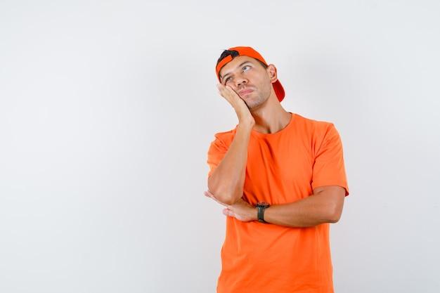 Jonge man in oranje t-shirt en pet, wang leunend op opgeheven handpalm en peinzend kijkt