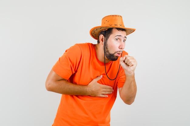 Jonge man in oranje t-shirt, hoed die lijdt aan hoest en er ziek uitziet, vooraanzicht.