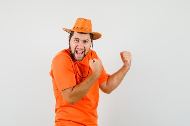 Jonge man in oranje t-shirt, hoed die winnaargebaar toont en er gelukkig uitziet, vooraanzicht.