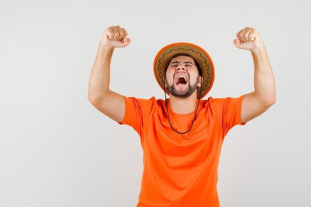 Jonge man in oranje t-shirt, hoed die winnaargebaar toont en er zalig uitziet, vooraanzicht.