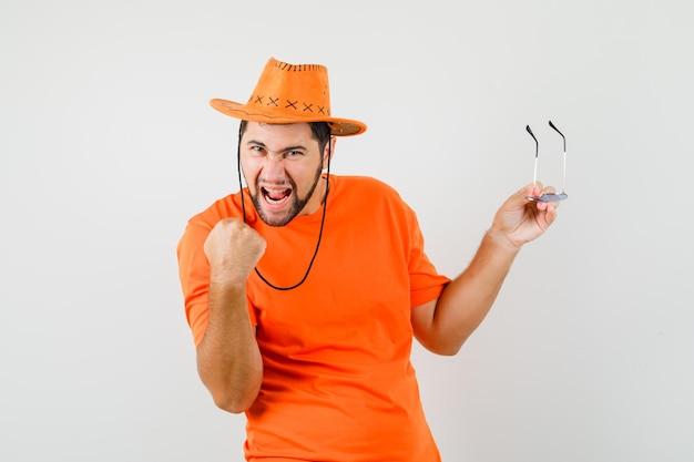 Jonge man in oranje t-shirt, hoed met bril met winnaargebaar en gelukkig, vooraanzicht.