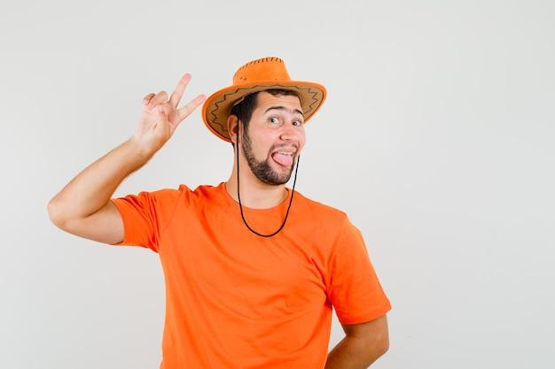Jonge man in oranje t-shirt, hoed met overwinningsteken, tong uitsteekt en er grappig uit, vooraanzicht.