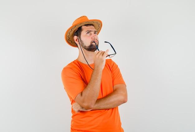 Jonge man in oranje t-shirt, hoed opkijkend terwijl hij een bril bijt en peinzend kijkt, vooraanzicht.