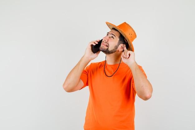 Jonge man in oranje t-shirt, hoed praten op mobiele telefoon en problemen met horen, vooraanzicht.