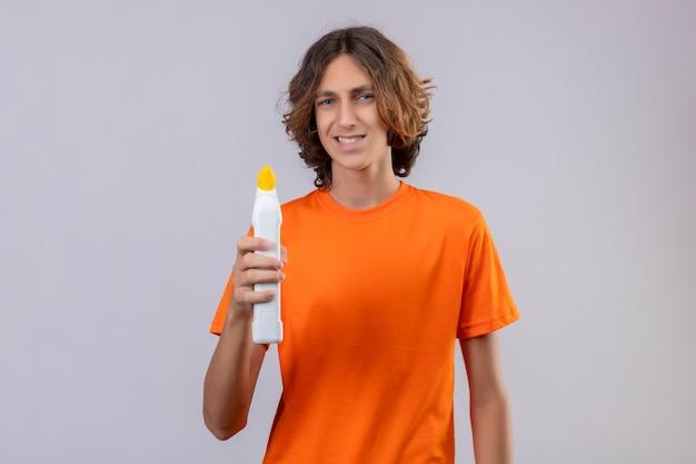 Jonge man in oranje t-shirt met fles schoonmaakproducten camera kijken met sceptische glimlach staande op witte achtergrond