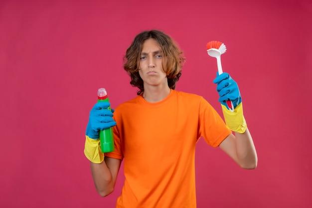 Jonge man in oranje t-shirt met rubberen handschoenen met fles schoonmaakbenodigdheden en schrobborstel camera kijken ontevreden met fronsend gezicht staande over roze achtergrond