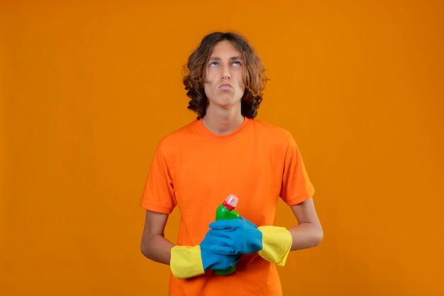 Jonge man in oranje t-shirt met rubberen handschoenen met fles schoonmaakproducten opzoeken met peinzende uitdrukking staande over gele achtergrond
