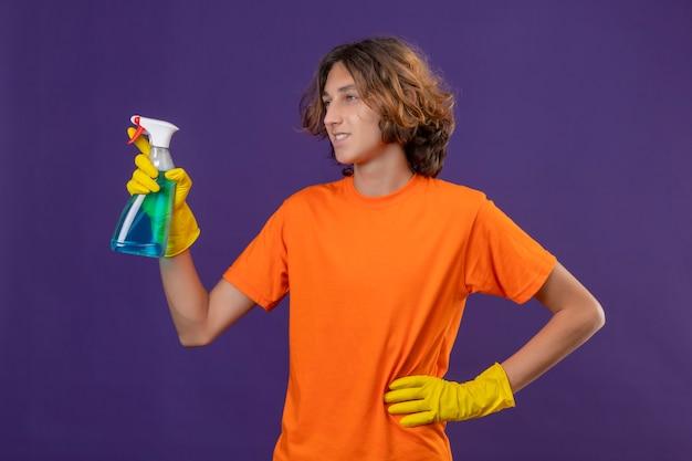 Jonge man in oranje t-shirt met rubberen handschoenen met reinigingsspray opzij kijken glimlachend met blij gezicht klaar om schoon te maken staande over paarse achtergrond