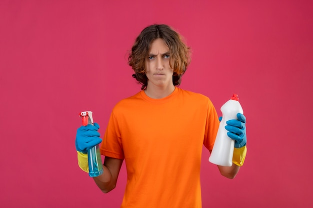 Jonge man in oranje t-shirt met rubberen handschoenen met schoonmaakspray en fles schoonmaakbenodigdheden camera kijken ontevreden met fronsend gezicht staande over roze achtergrond