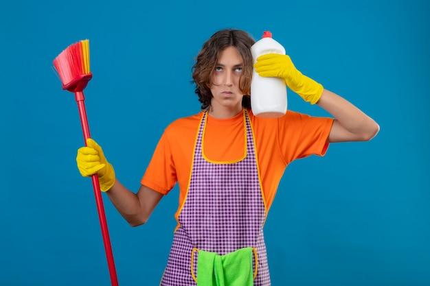 Jonge man in oranje t-shirt met schort en rubberen handschoenen met dweil en fles schoonmaakbenodigdheden opzoeken met ernstig gezicht op zoek angstig staande over blauwe achtergrond