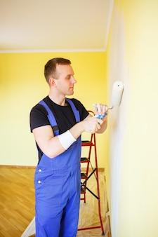 Jonge man in overall houdt een verfroller vast. gereedschapsaccessoires voor de renovatie van een appartementkamer. woningrenovatieconcept