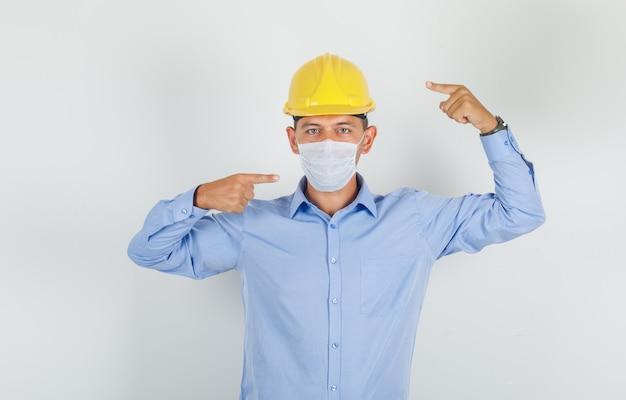 Jonge man in overhemd, helm die zijn masker toont en omhoog wijst en voorzichtig kijkt