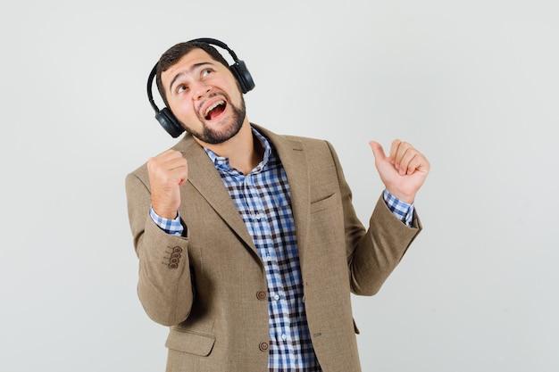 Jonge man in overhemd, jasje genieten van muziek met koptelefoon en op zoek vrolijk, vooraanzicht.