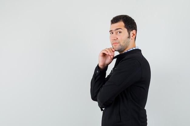 Jonge man in overhemd, jasje staande in denken pose en verstandig op zoek.
