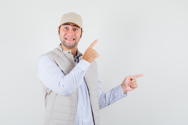 Jonge man in overhemd, mouwloos jasje, pet die opzij wijst en er vrolijk uitziet, vooraanzicht.