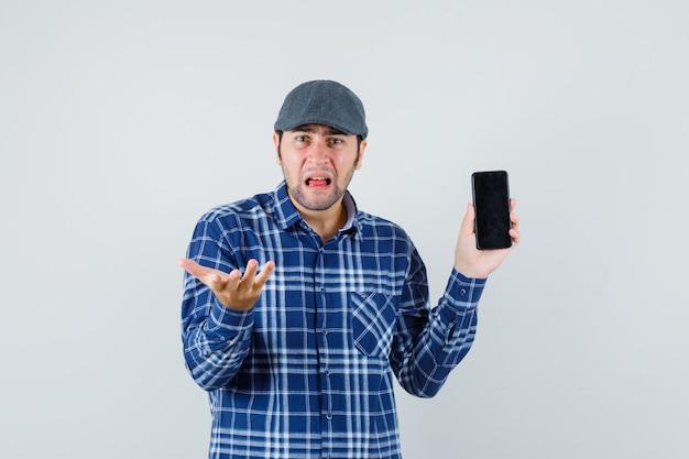 Jonge man in overhemd, pet die mobiele telefoon houdt en verward, vooraanzicht kijkt.