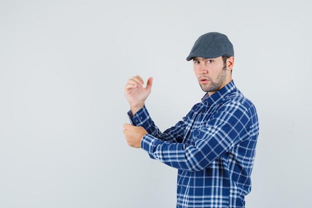 Jonge man in overhemd, pet die mouw van zijn overhemd losknoopt en peinzend, vooraanzicht kijkt.