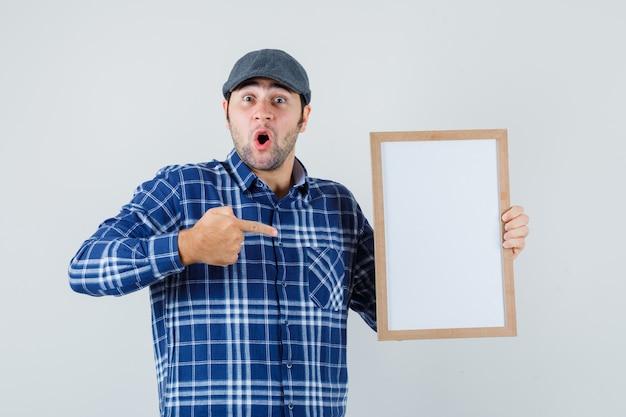Jonge man in overhemd, pet wijzend op leeg frame en op zoek verrast, vooraanzicht.