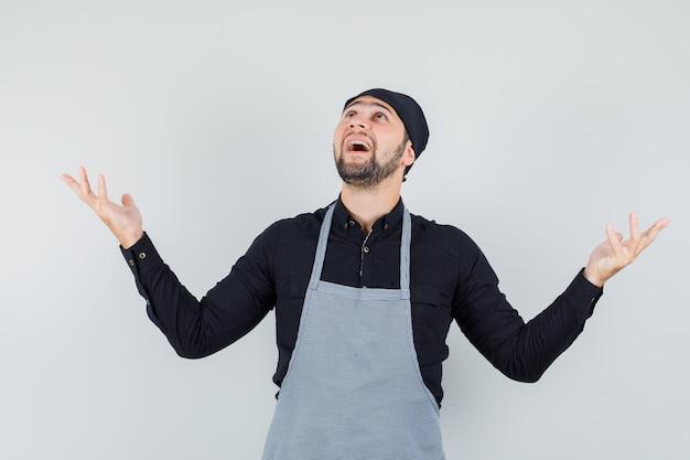Jonge man in overhemd, schort die handen opheft terwijl hij omhoog kijkt en dankbaar kijkt, vooraanzicht.