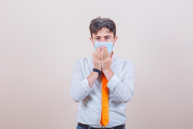 Jonge man in overhemd, stropdas, masker, spijkerbroek die lijdt aan hoest en er ziek uitziet