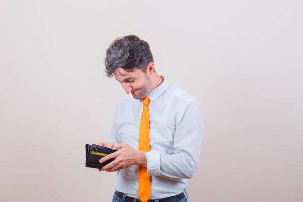 Jonge man in overhemd, stropdas, spijkerbroek die in de portemonnee kijkt en er vrolijk uitziet
