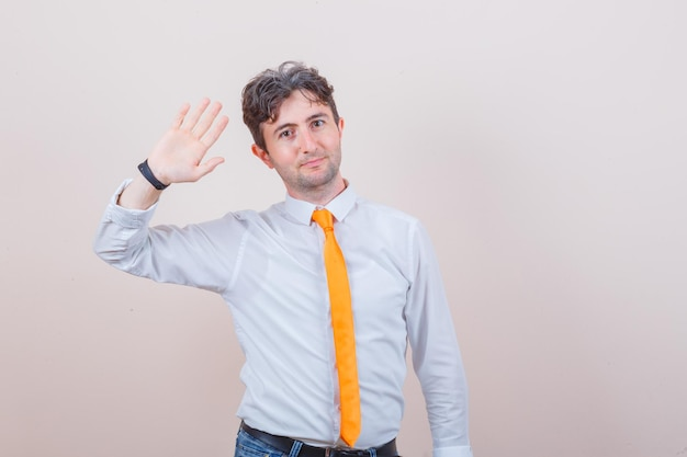 Jonge man in overhemd, stropdas, spijkerbroek die met de hand zwaait om hallo of tot ziens te zeggen en er vrolijk uitziet