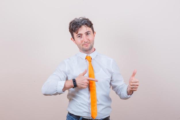 Jonge man in overhemd, stropdas, spijkerbroek die naar zijn duim wijst en er zelfverzekerd uitziet