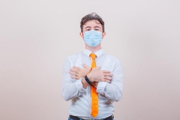 Jonge man in overhemd, stropdas, spijkerbroek, masker met gekruiste handen op de borst